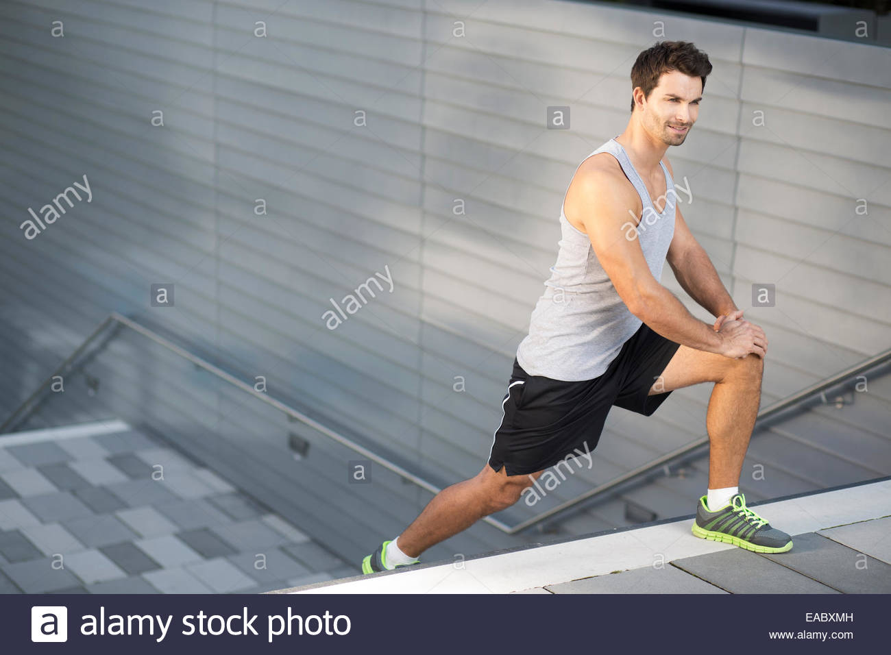 Sportsman doing stretching exercises on a staircase - Stock Image