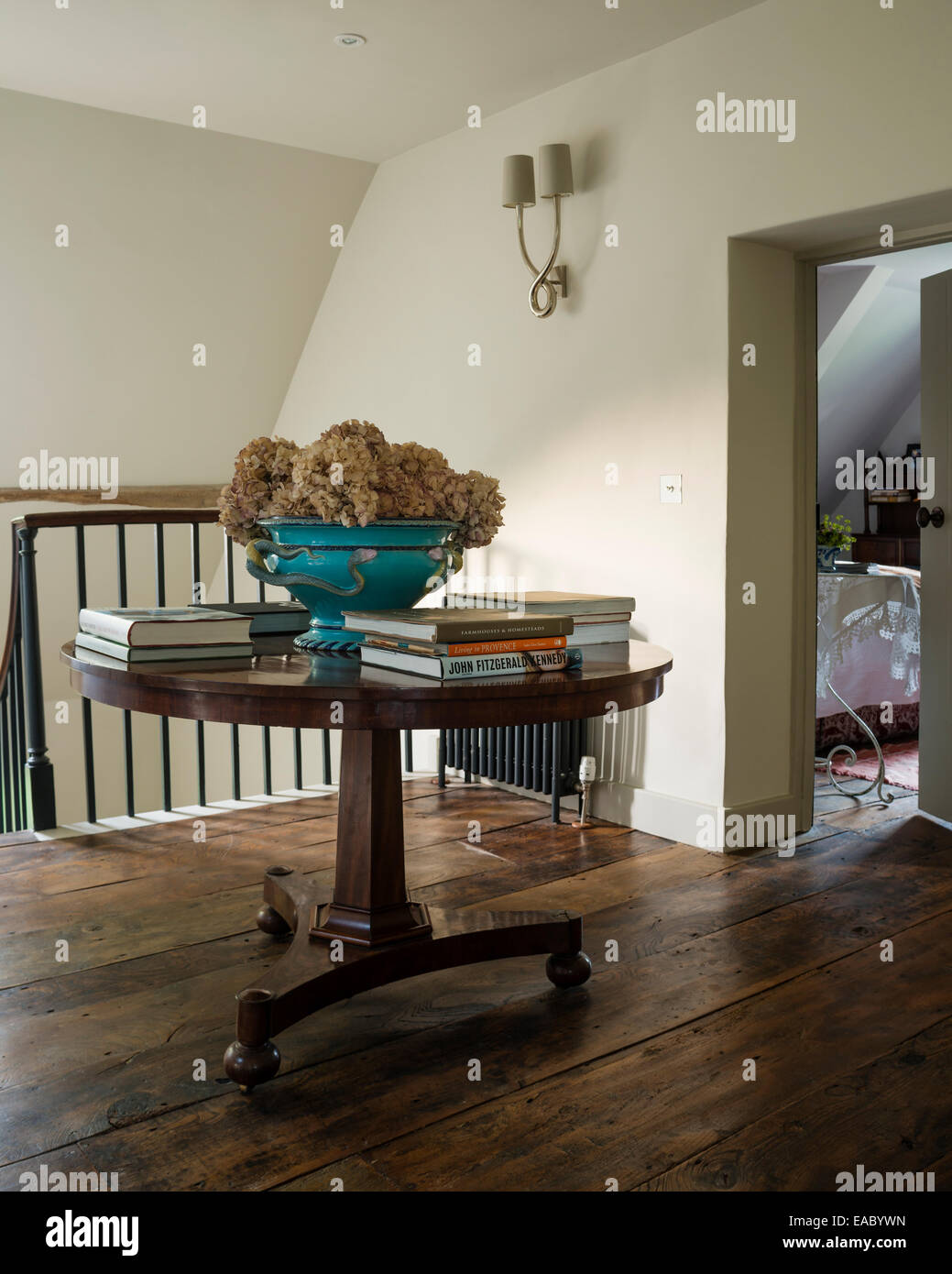 Round table with books and dried hydrangeas on upstairs landing with elm flooring - Stock Image