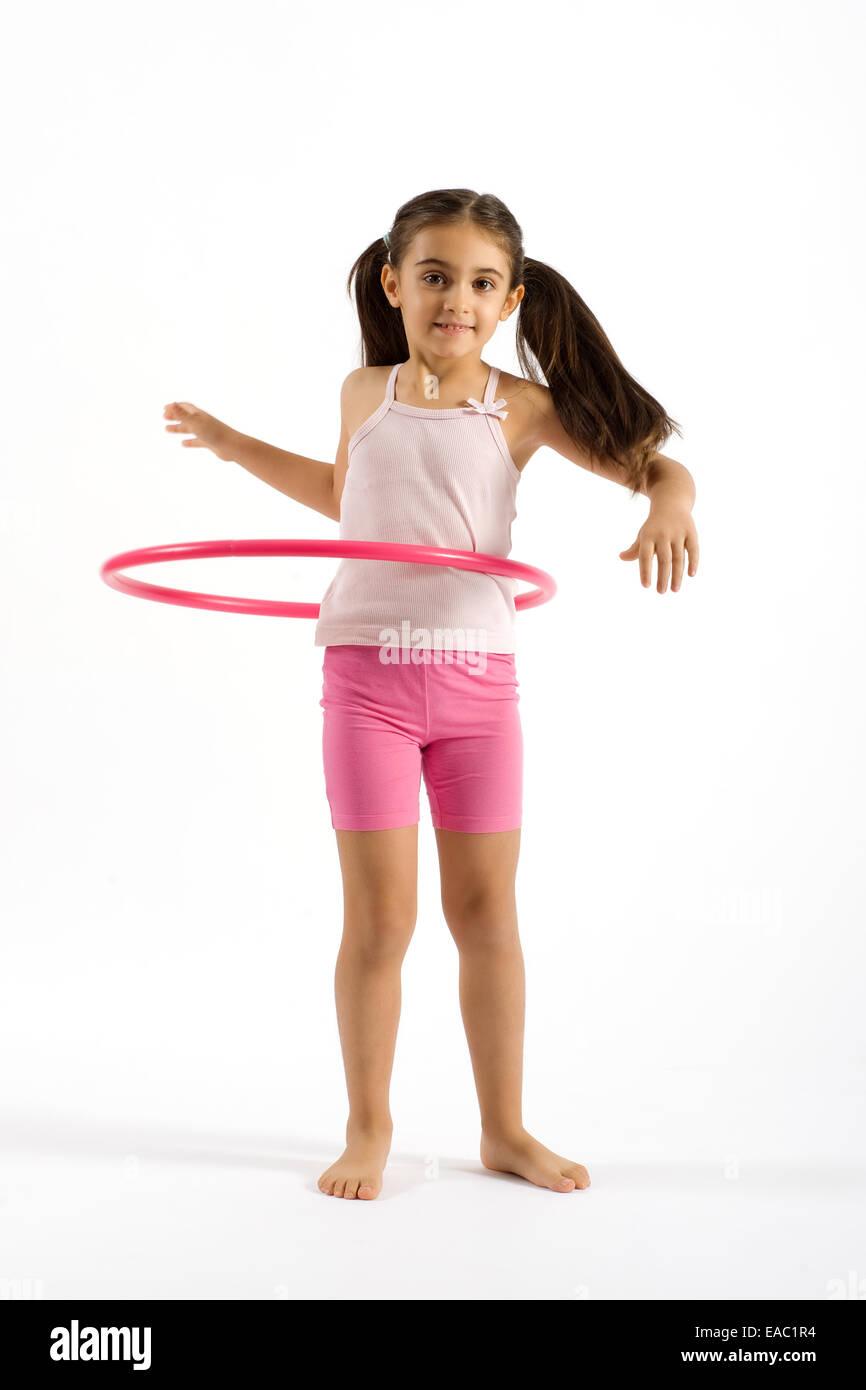 Young Pretty Girl Playing Pink Hula Hoop - Stock Image