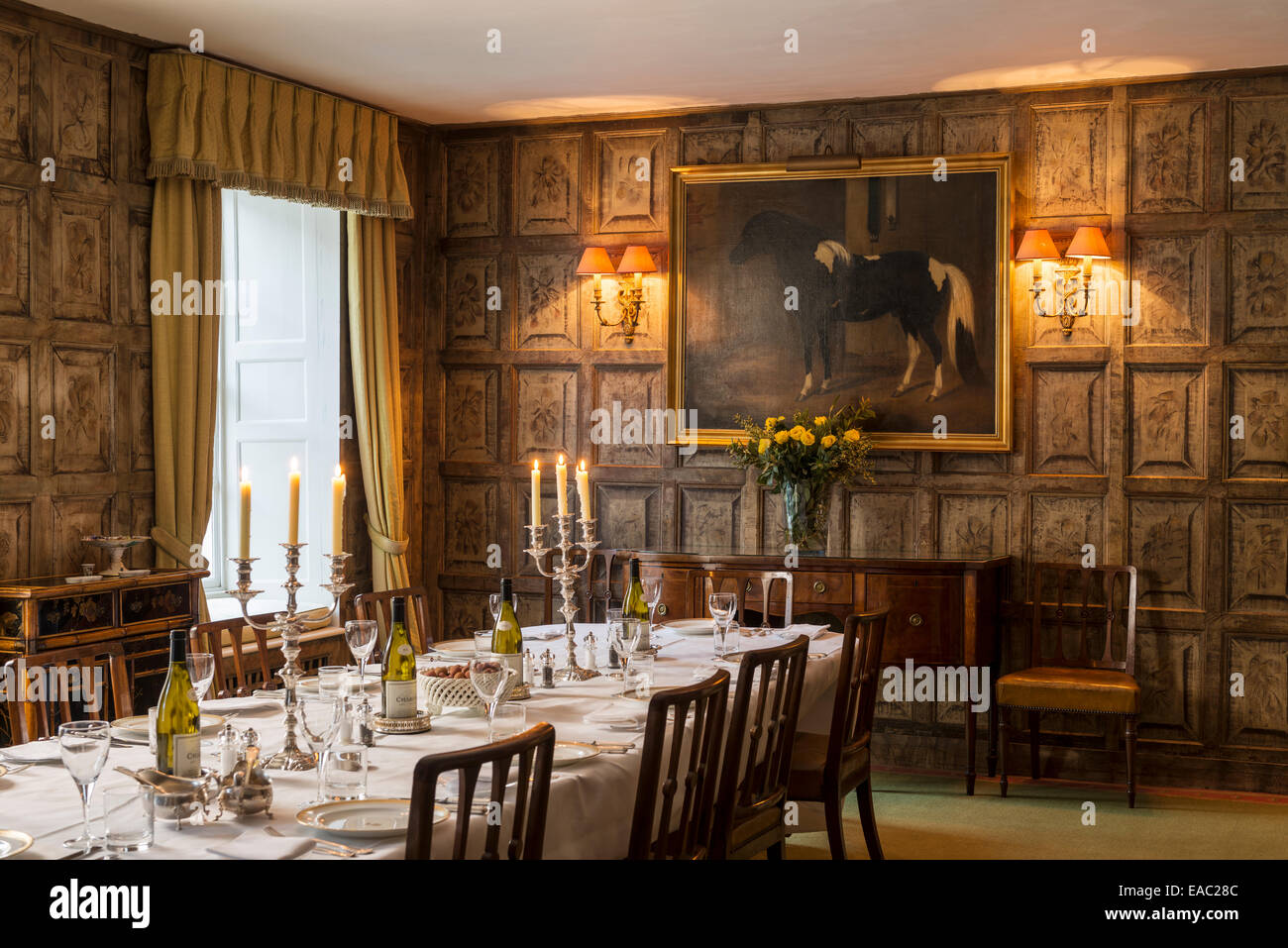 Original Jacobean wall panels in dining room with gilt framed piebald pony painting by W Elstob Marshall Stock Photo