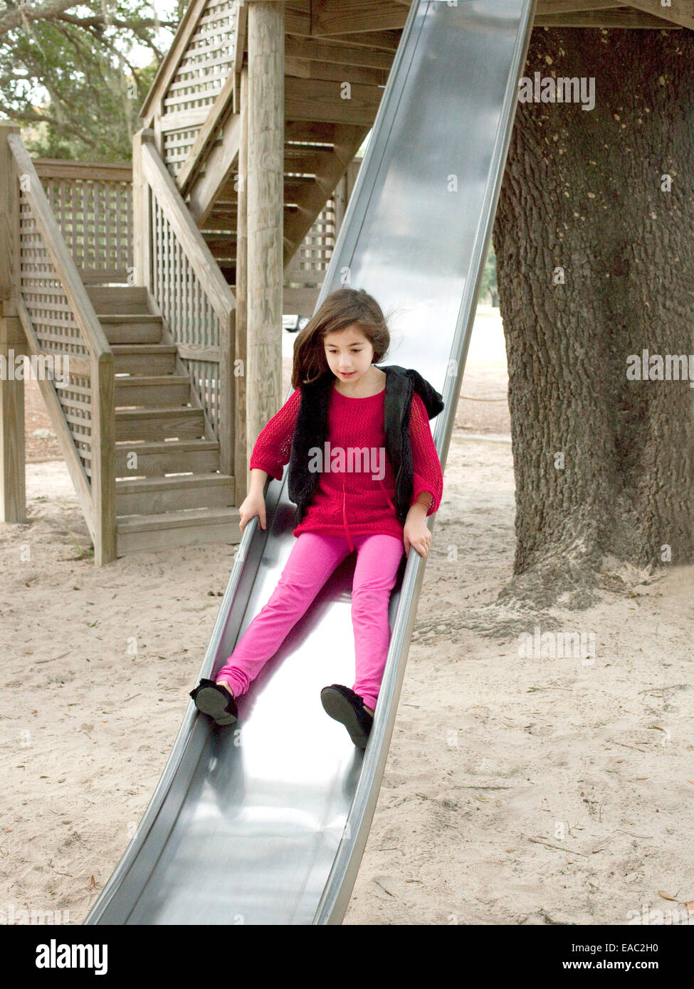 young girl on slide in playground - Stock Image