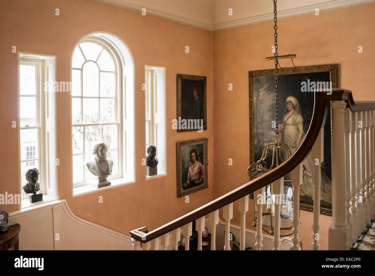 Portraits and busts look down onto stairwell with banister - Stock Image
