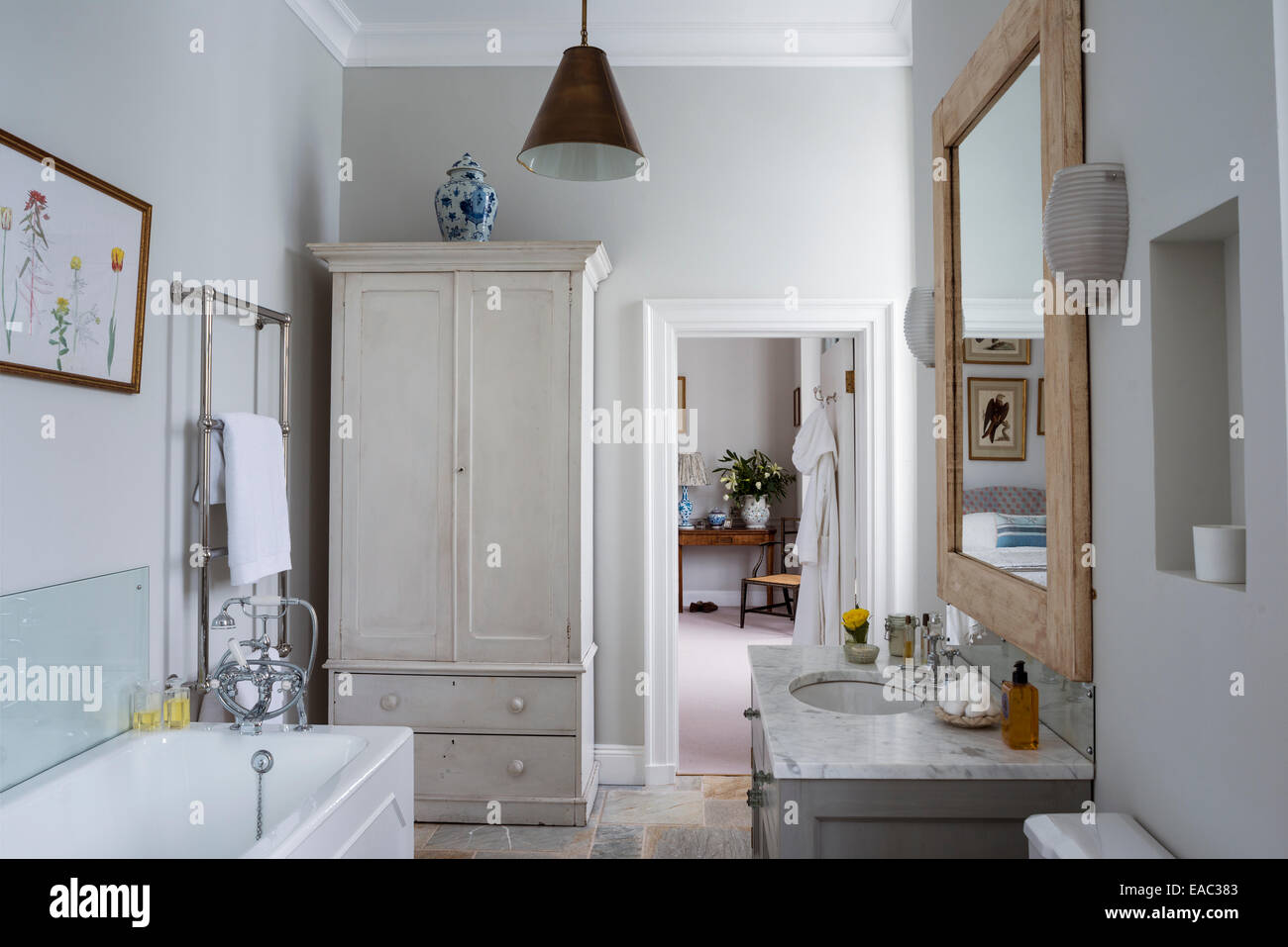 Marble-topped hand basin unit from Pymalion Interiors in bathroom with wooden wardrobe - Stock Image