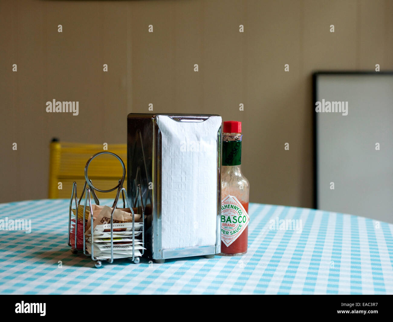 blue gingham wax table clothe with napkins and condiments at diner - Stock Image