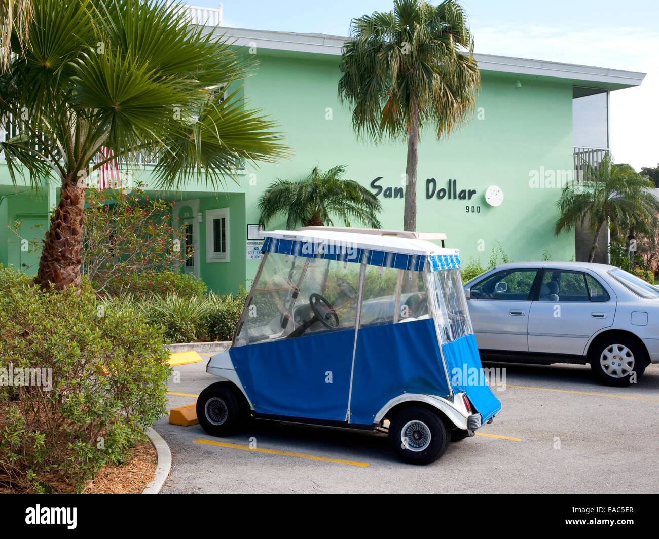 Covered golf cart in motel parking lot - Stock Image