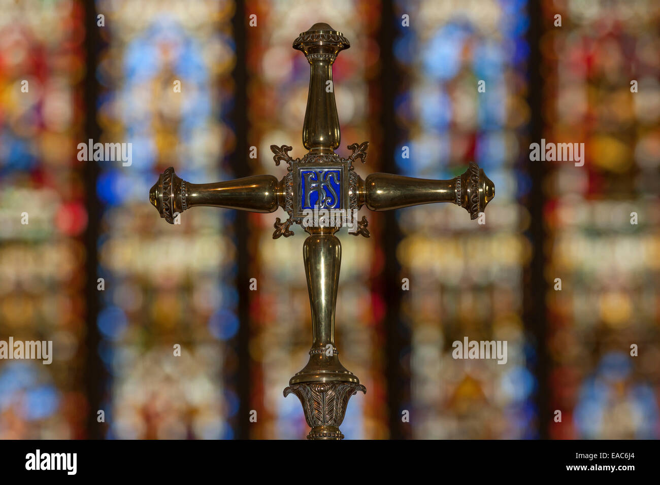 Decorated brass cross against a background of stained glass windows - Stock Image