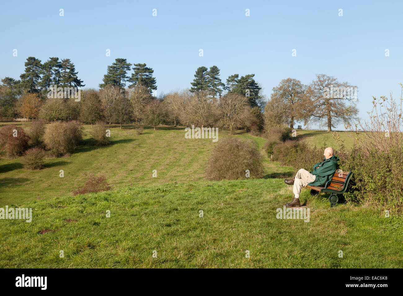 A man sitting on a bench looking out over English countryside, Welcombe Hills, Warwickshire UK - Stock Image