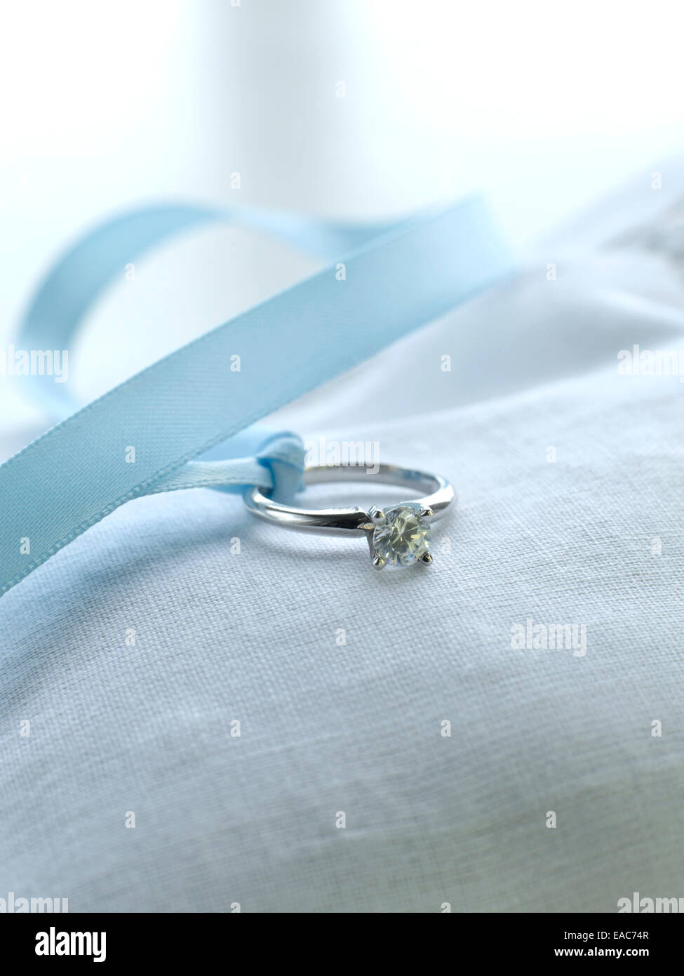 diamond wedding ring with silk ribbon on pillow marriage vows gold silver - Stock Image