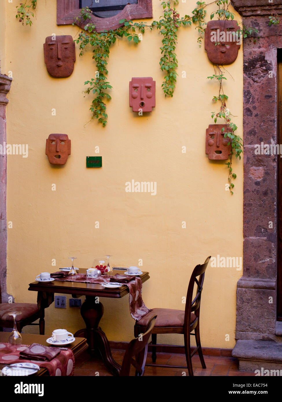 courtyard dining room in mexico with ceramic masks - Stock Image