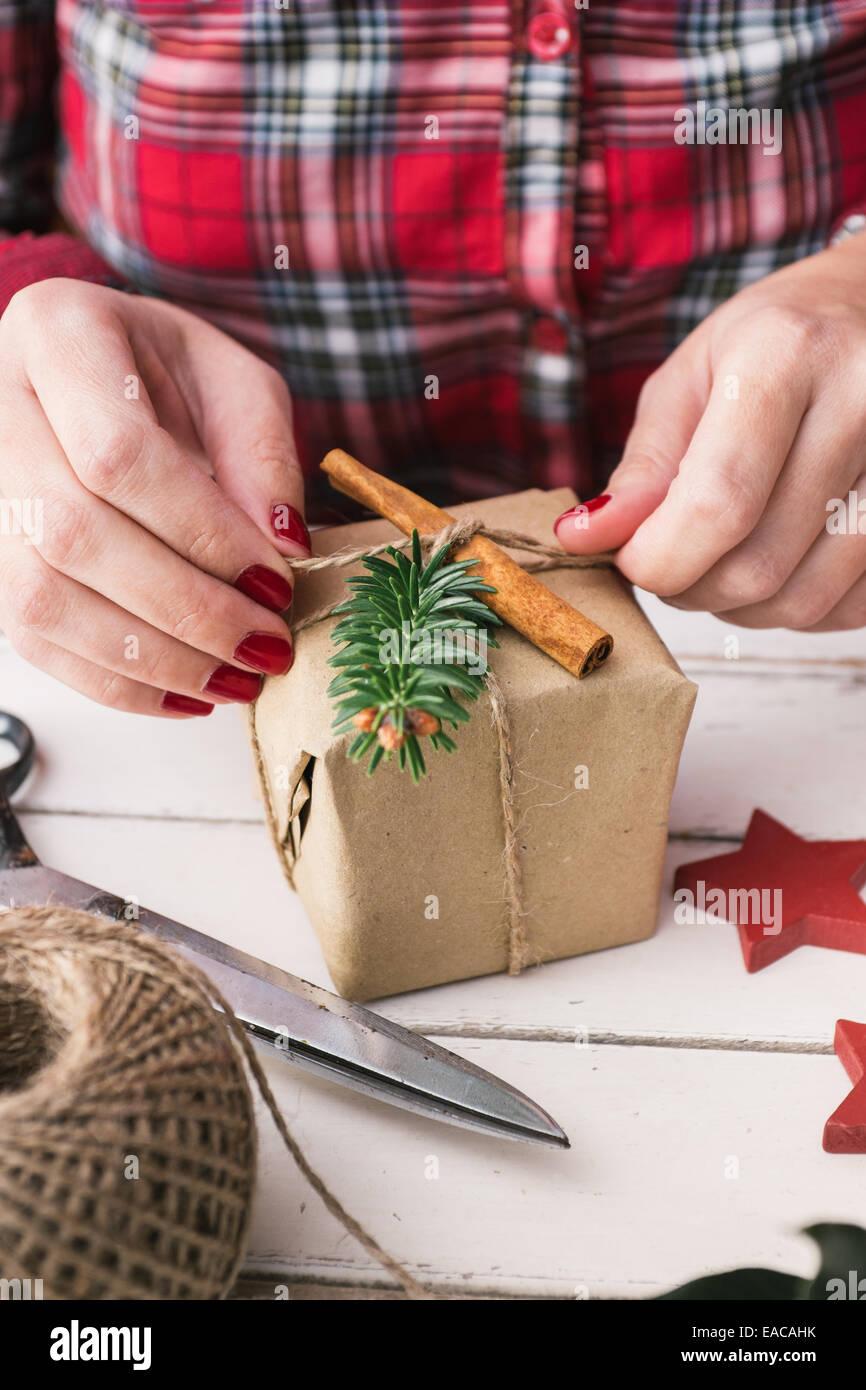 Woman wrapping cool christmas gift - Stock Image