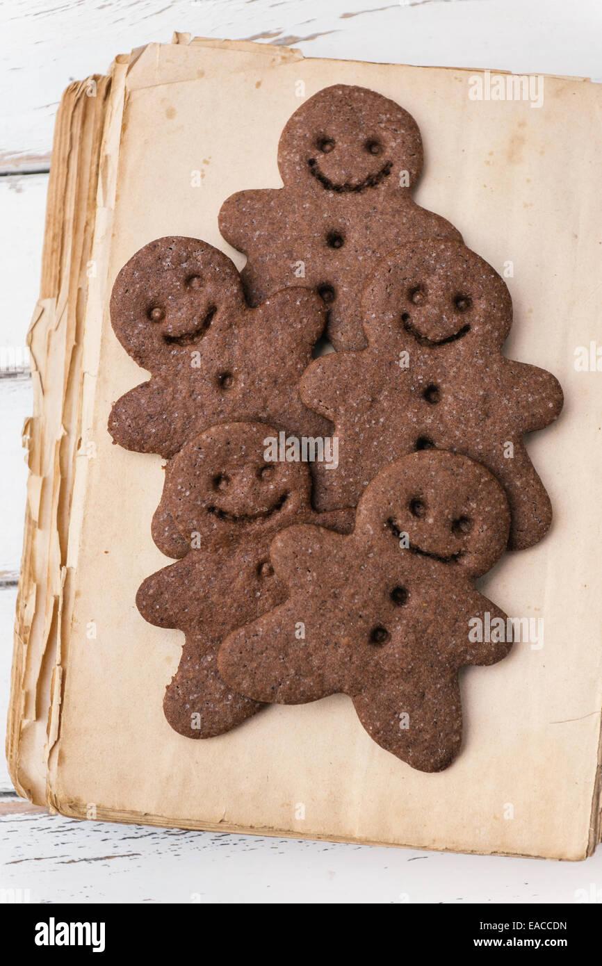 Gingerbread men on vintage cookbook - Stock Image