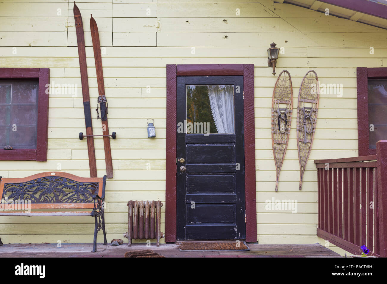 Old house with skis and snowshoes hanging by the front door; McCarthy, Alaska, United States of America - Stock Image