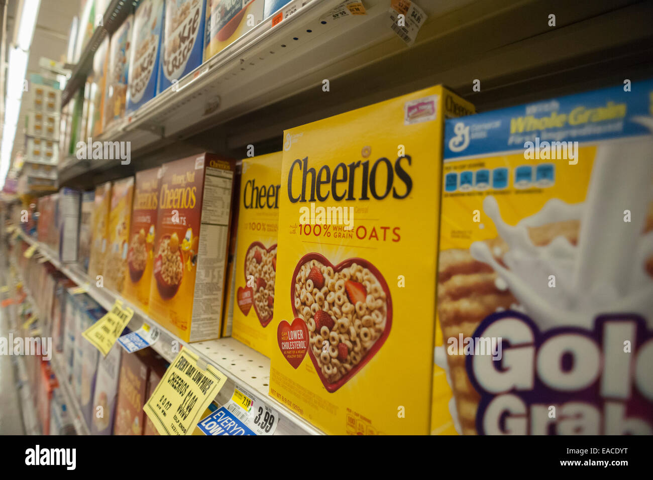 Boxes of General Mills breakfast cereals including Cheerios on supermarket shelves - Stock Image