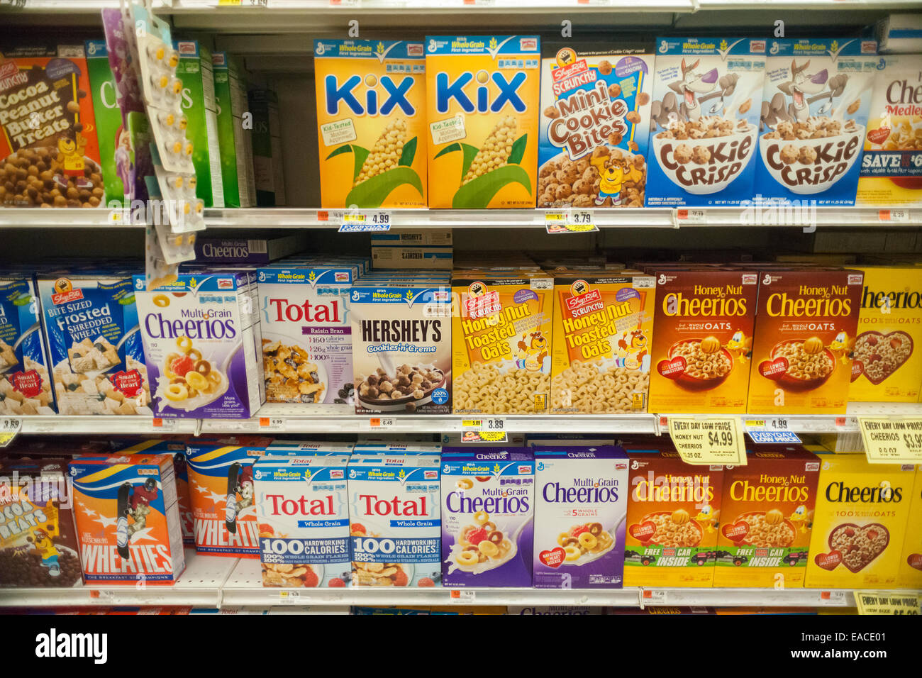 Boxes of General Mills breakfast cereals mixed in with house brand similar on supermarket shelves - Stock Image