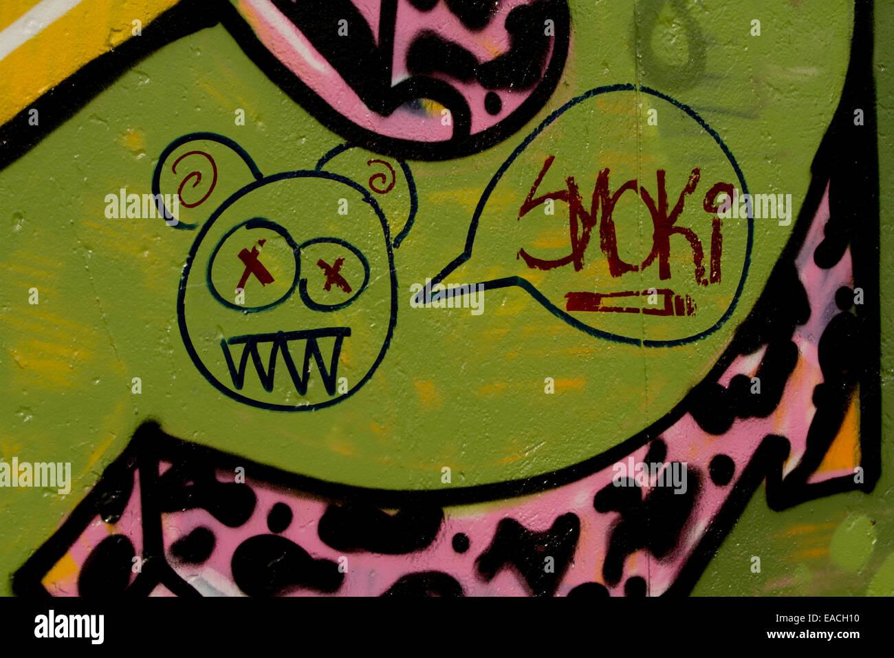 Graffiti cartoon face smoki joint colourful wall - Stock Image