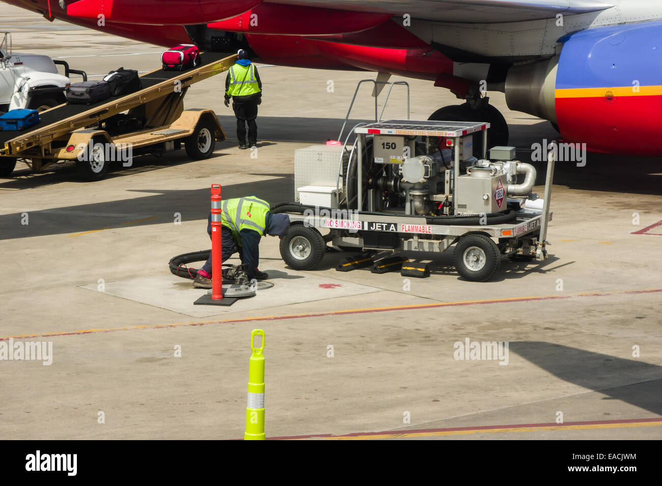 Southwest Airlines jet being refueled and loaded with luggage. - Stock Image