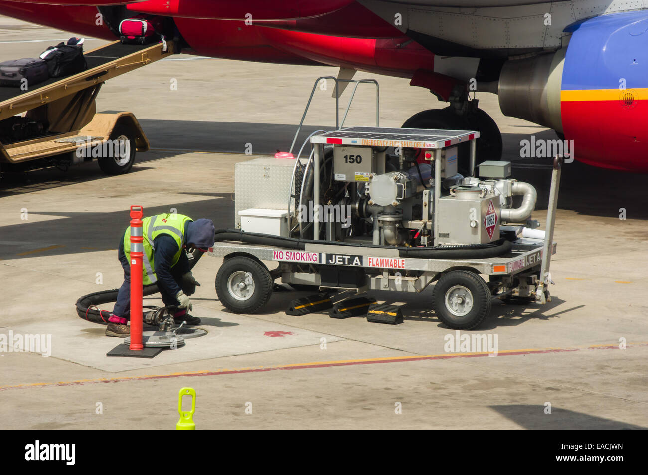 Ground crew using a mobile fuel pump to fill the tanks of a Southwest Airlines plane. - Stock Image