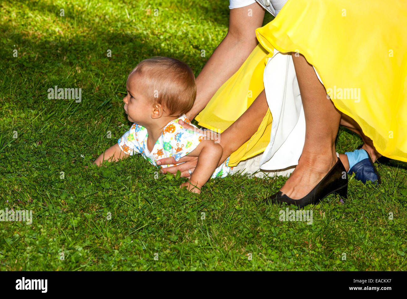 mother in a yellow dress, son, toddler, garden - Stock Image