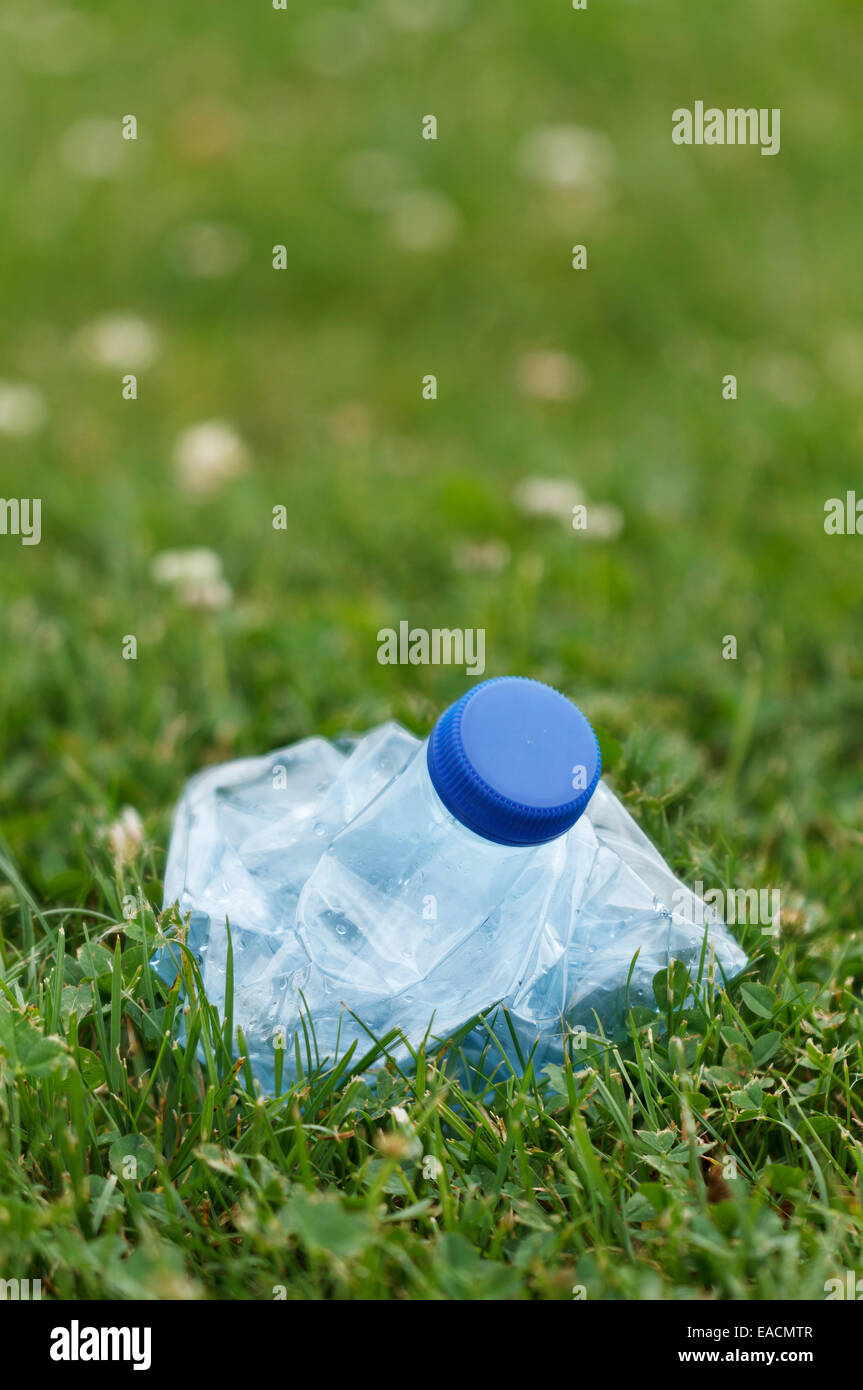 plastic water bottle compressed with hands - Stock Image