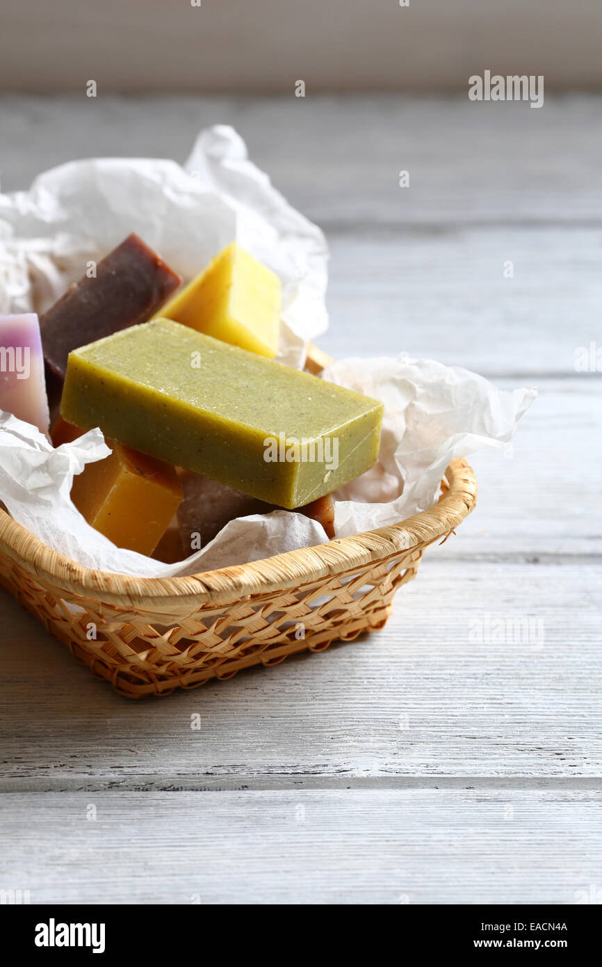 Handmade soap in a wicker basket, wooden background - Stock Image