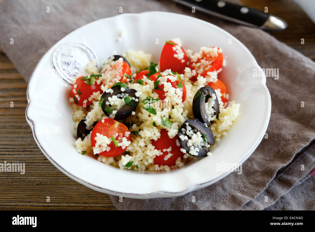 Delicious salad couscous with vegetables and olives on a plate, close up - Stock Image