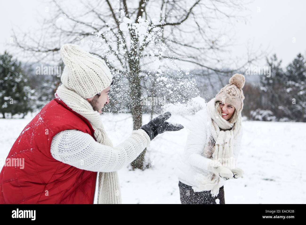 Happy couple doing a snowball fight together in winter - Stock Image