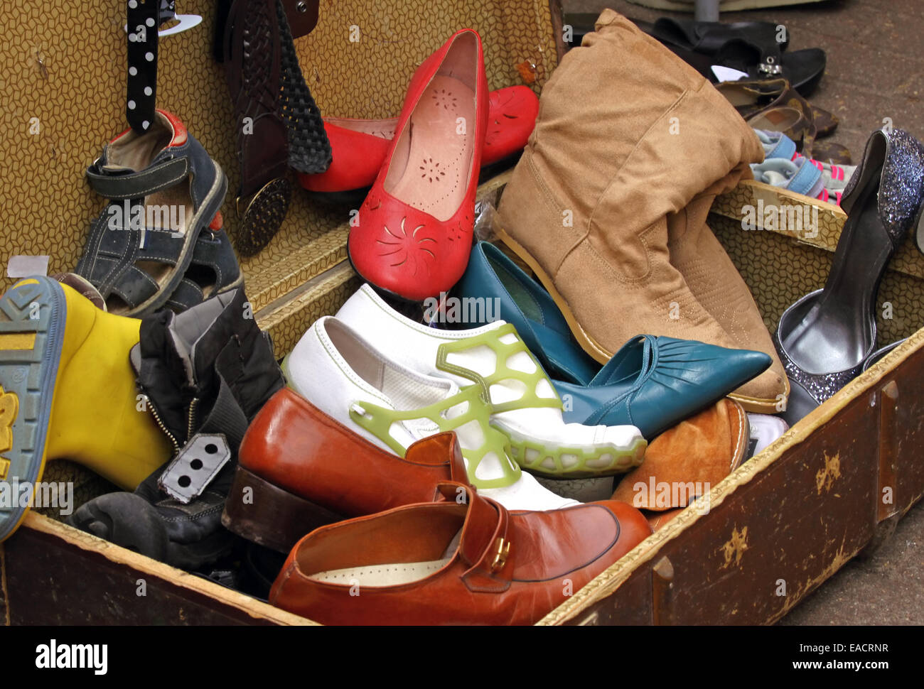 Suitcase full of old worn out shoes at flea market - Stock Image