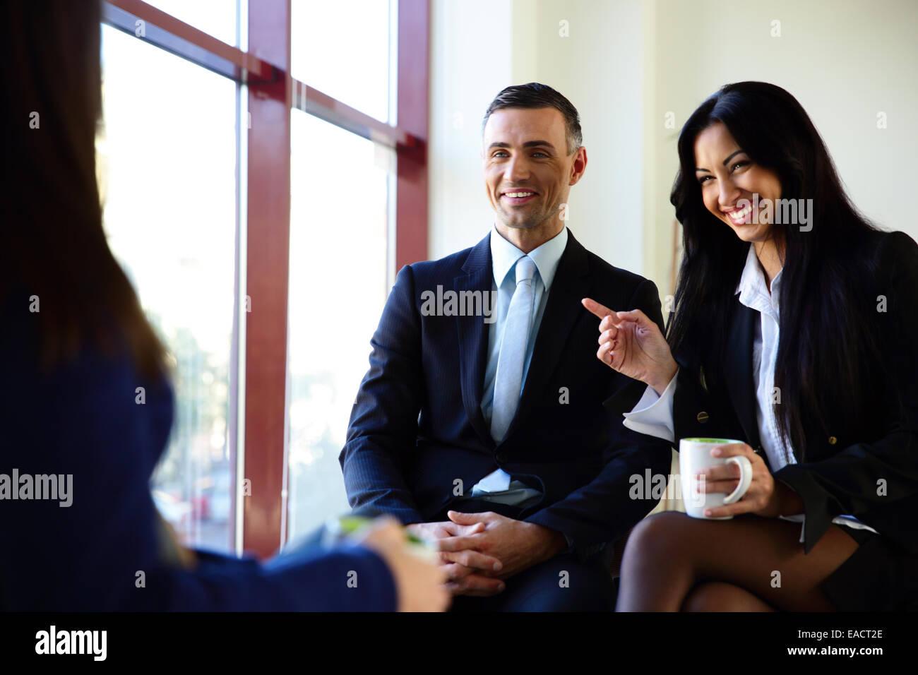 Smiling businesspeople having coffee break in office - Stock Image