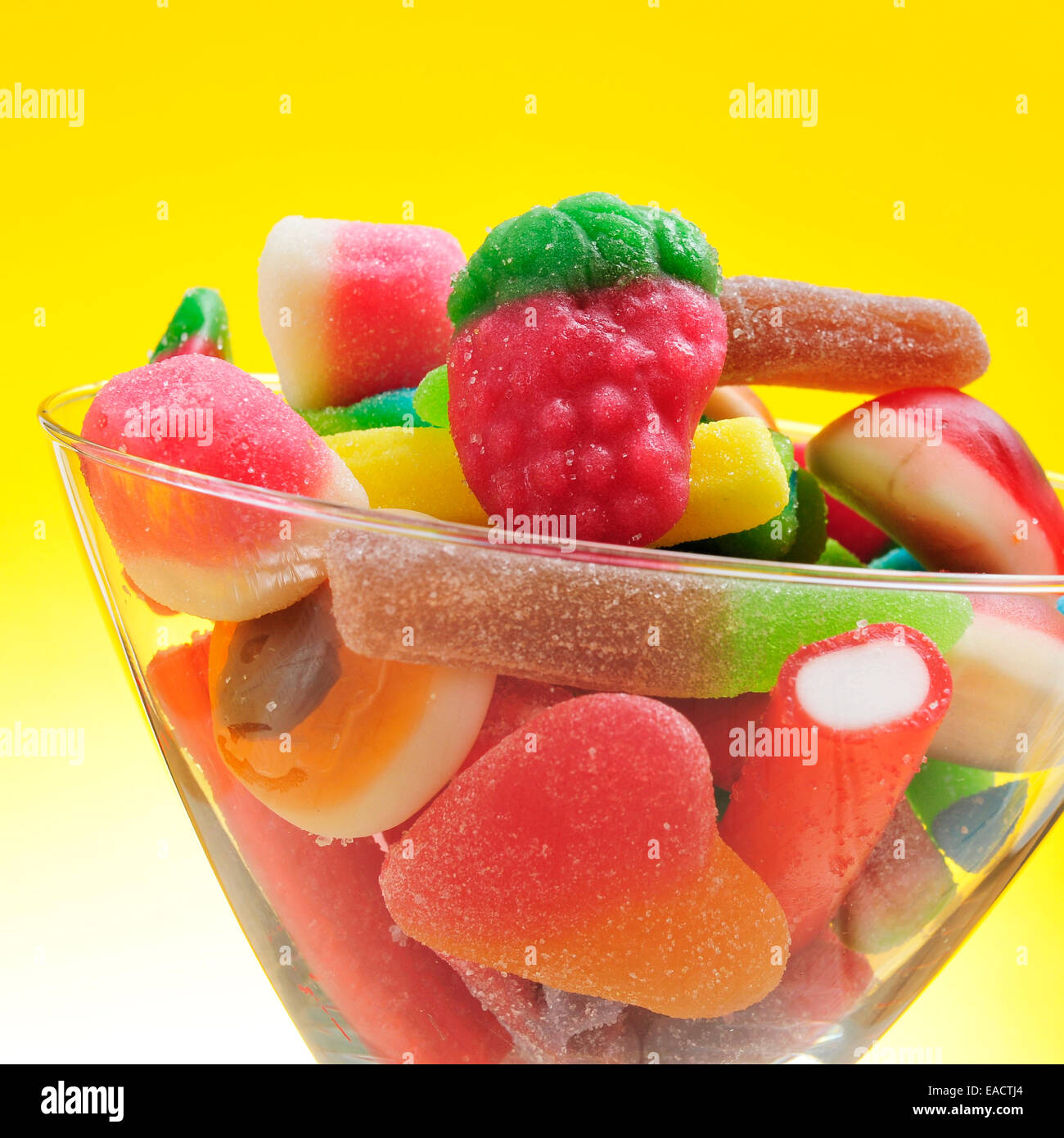 closeup of a pile of different candies in a glass on a yellow background Stock Photo