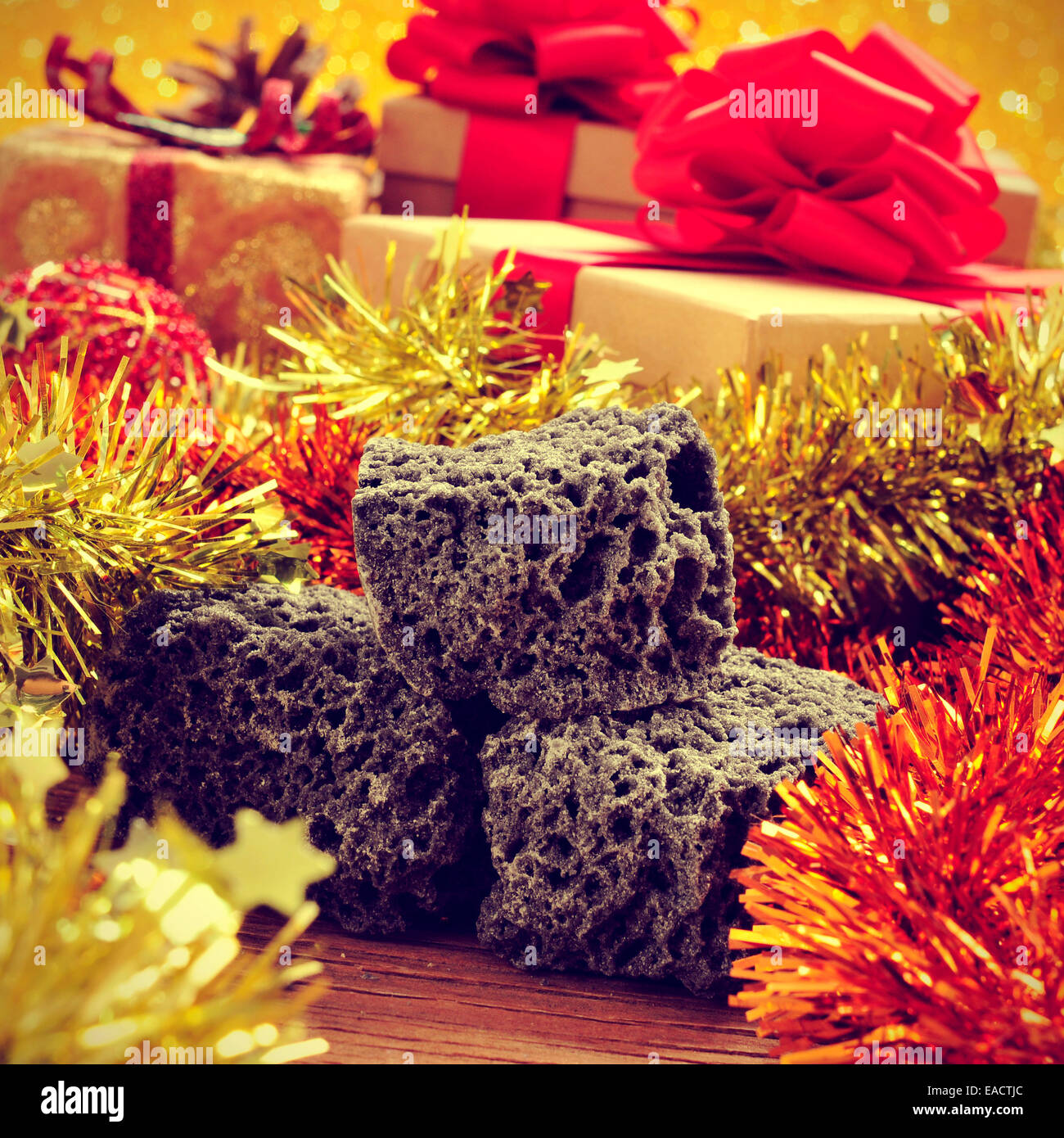 some lumps of candy coal and some christmas ornaments and gifts on a rustic wooden table, with a retro effect - Stock Image