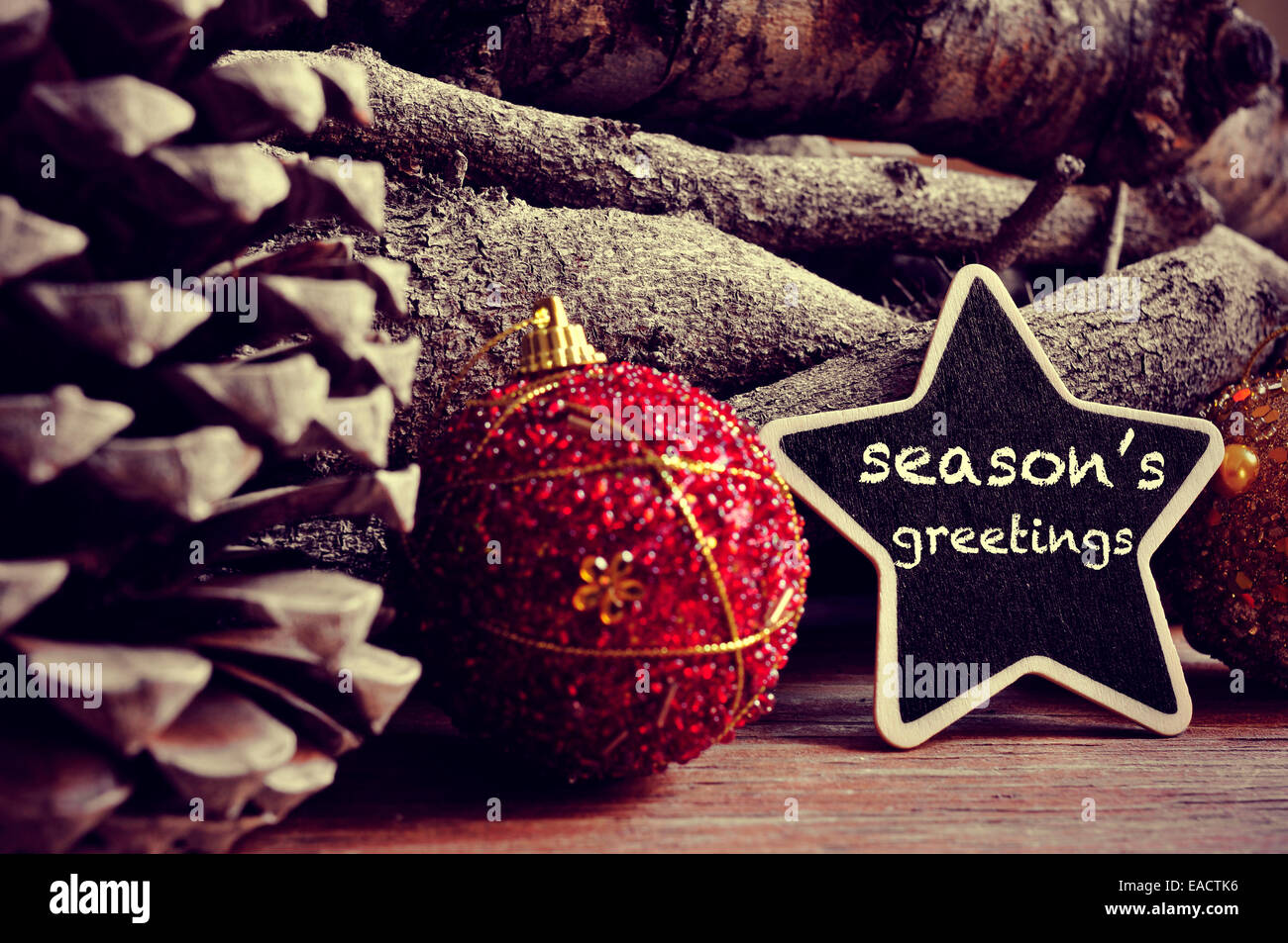 the text seasons greetings written in a star-shaped blackboard and some christmas balls, pinecones and a pile of - Stock Image