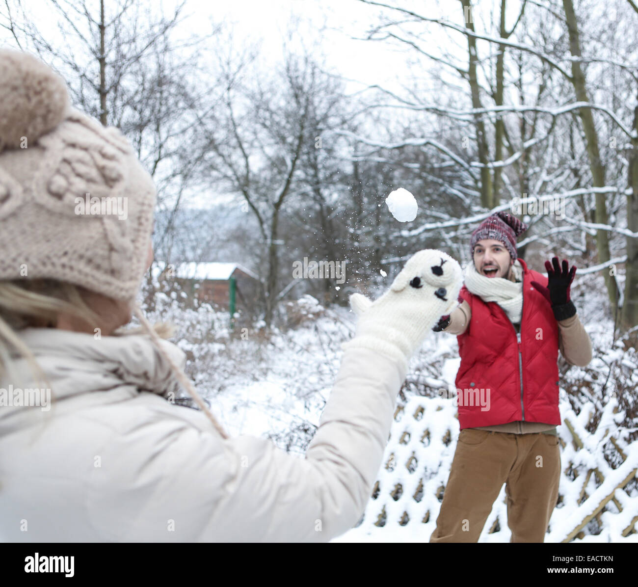 Man and woman doing a snowball fight in winter - Stock Image