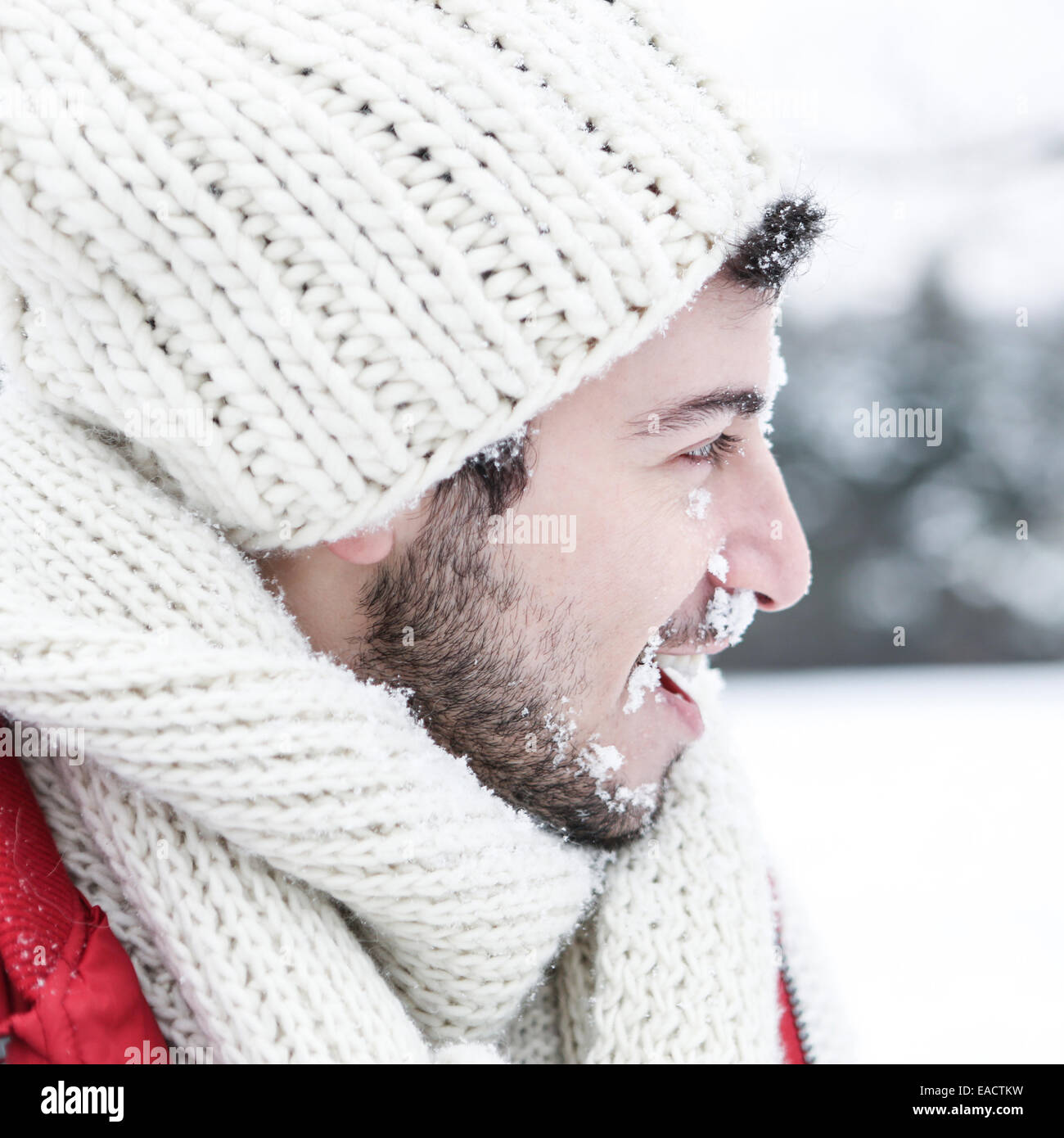 Man in winter with snow in his face at a snowball fight - Stock Image