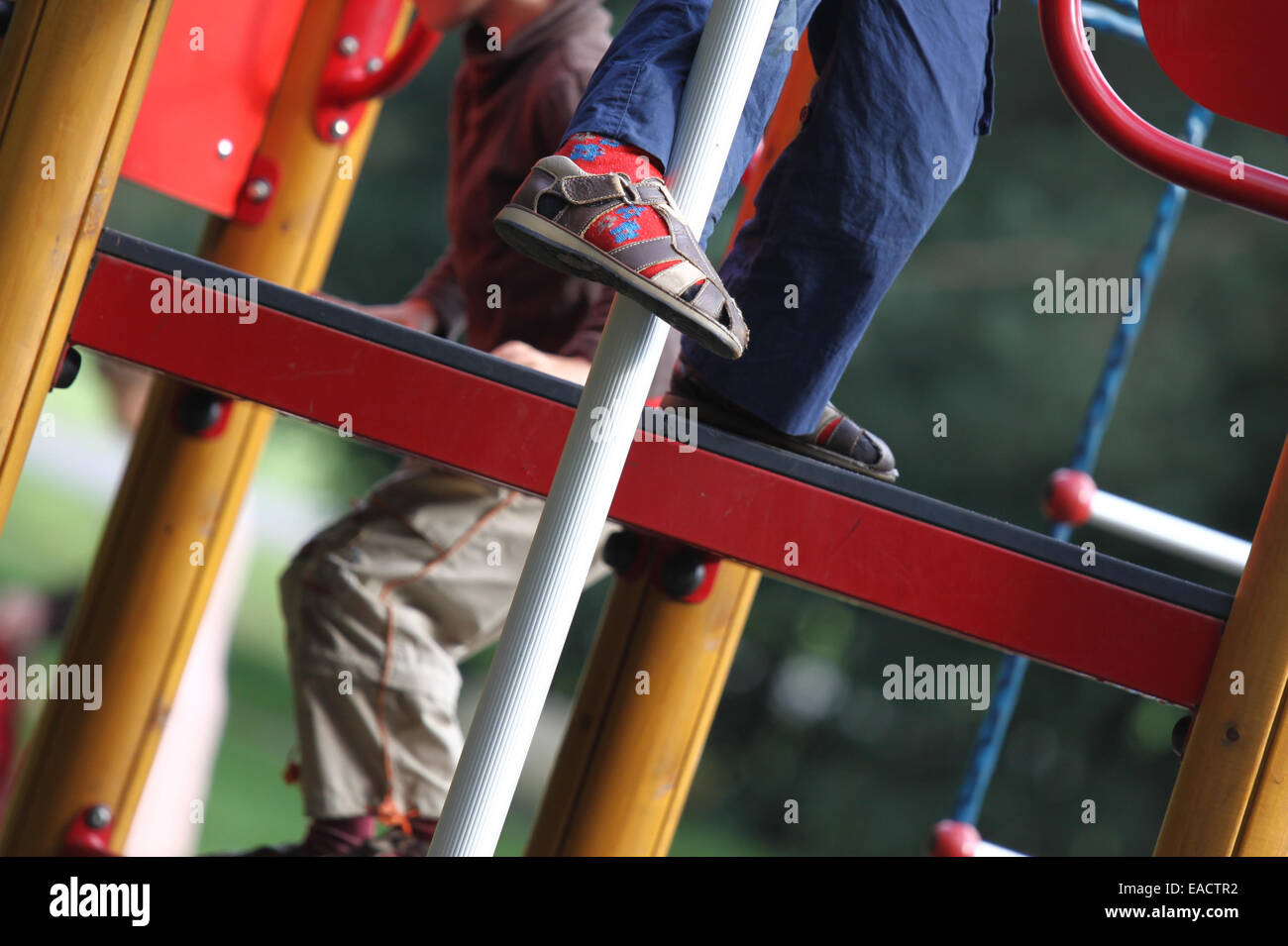 Little boy's leg is seen as he plays at colorful playground - Stock Image