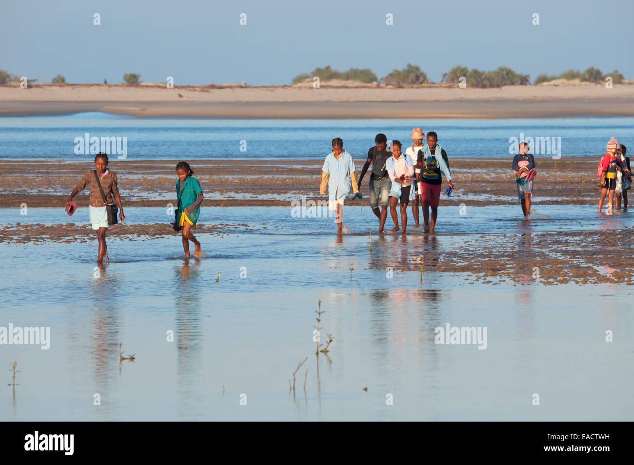 Malagasy people crossing the water, Morondava, Toliara province, Madagascar - Stock Image