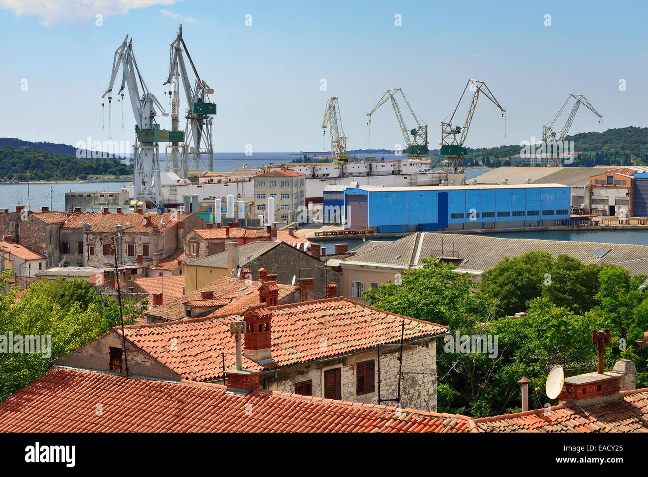 View over the rooftops of the city on the loading cranes in the port, Pula, Istria, Croatia, Europe - Stock Image