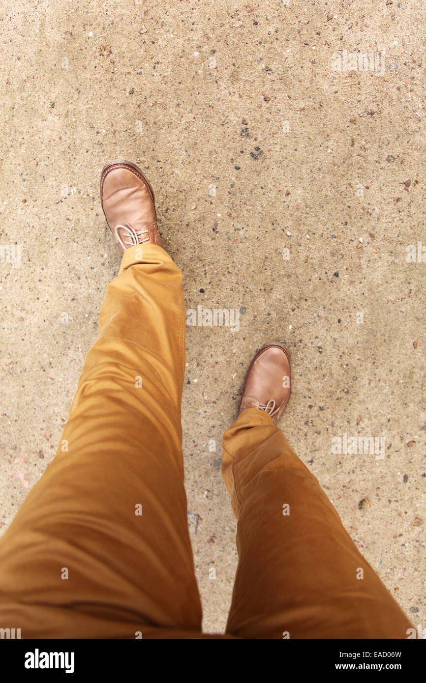 Man's feet in shoes walking on a park lane. Top view. - Stock Image