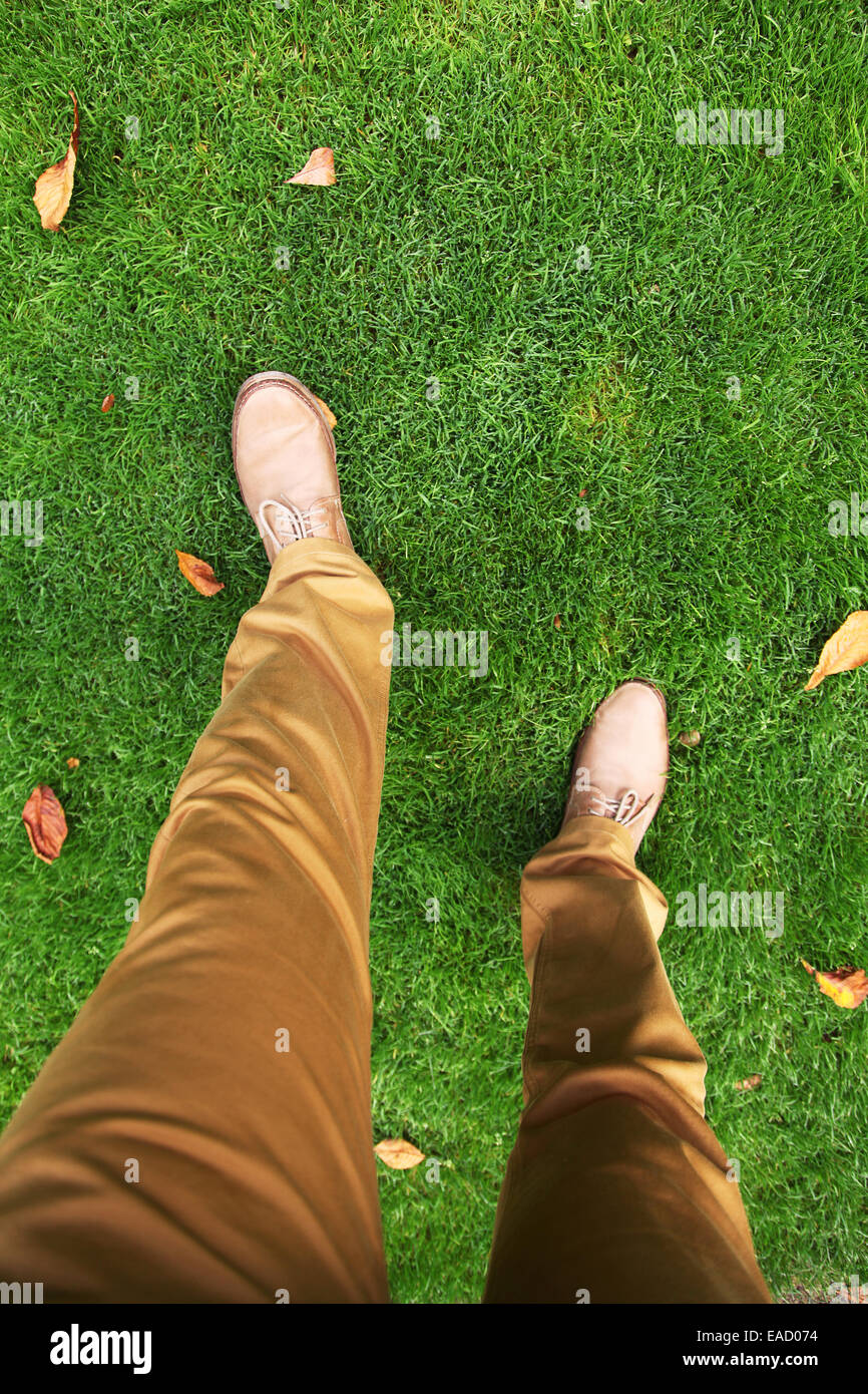 Walking in the park. Man's feet in shoes on the grass. Top view. - Stock Image