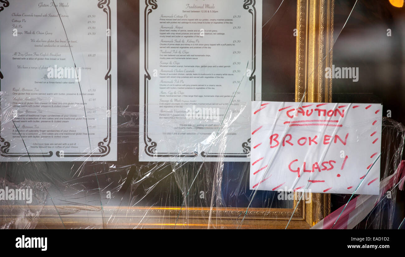 'Caution Broken Glass' sign on cracked windows shop fronts with hand written warning signs - Stock Image