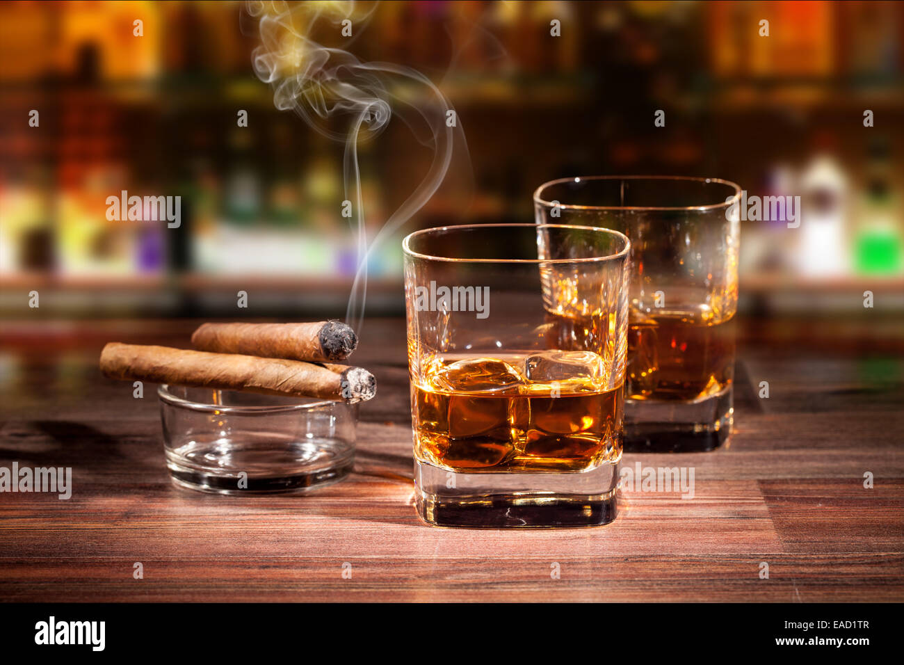 Whiskey drink with smoking cigar on wooden table - Stock Image
