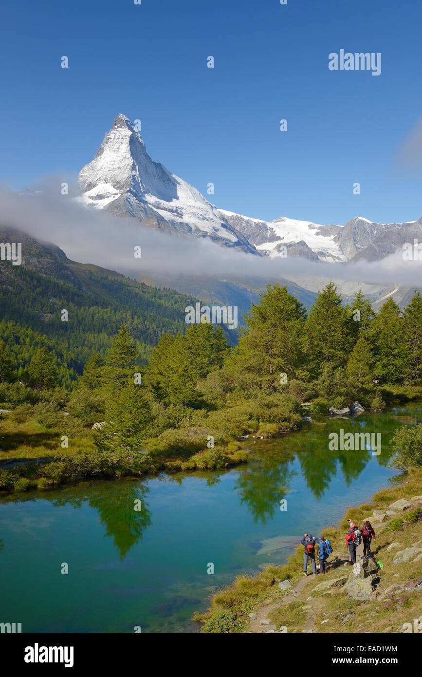 Hikers taking photographs of the Matterhorn with Lake Grindjisee in the foreground, Zermatt, Canton of Valais, Switzerland - Stock Image