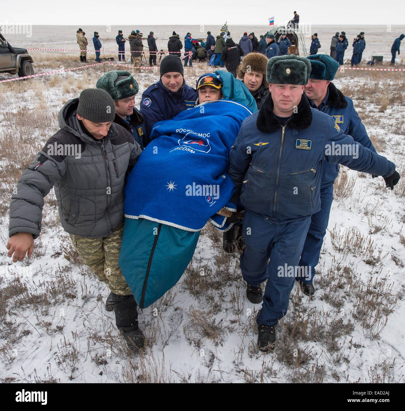 ISS Expedition 41 Commander Max Suraev of the Russian Federal Space Agency is carried to the medical tent outside - Stock Image