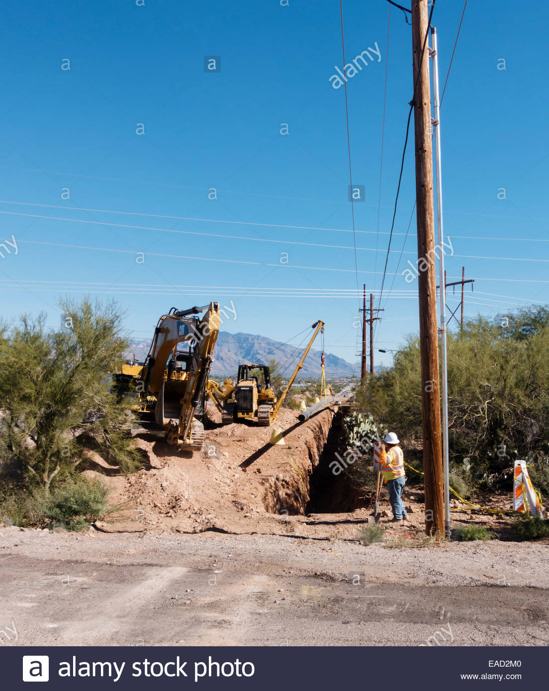Caterpillar CAT D5K2 pipelayer holding natural gas pipeline 316E excavator foreground Arizona 2 people visible - Stock Image