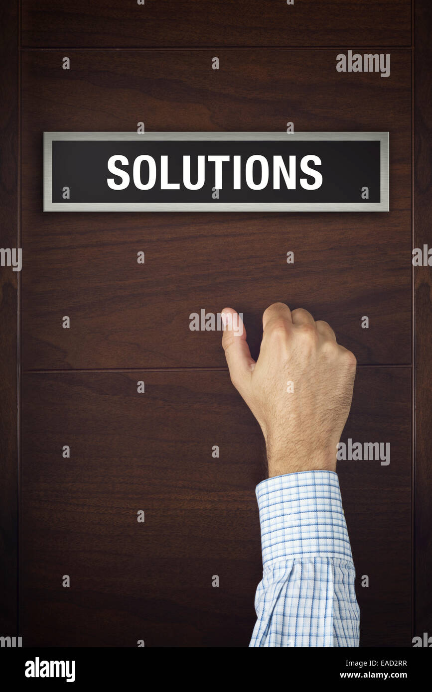 Male hand is knocking on Solutions bureau door, conceptual image. - Stock Image