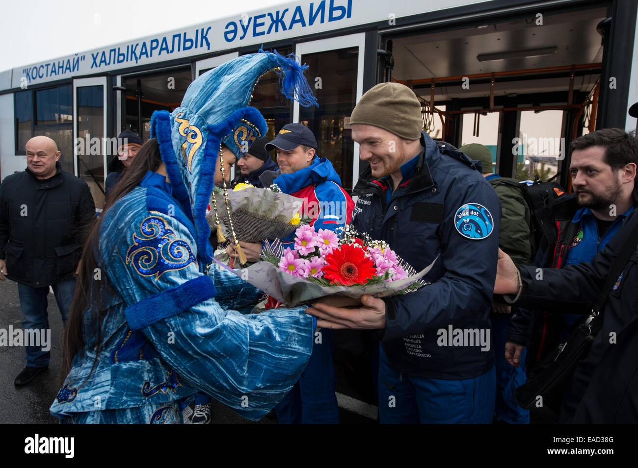 A woman in ceremonial Kazakh dress presents flowers to ISS Expedition 41 crew member Alexander Gerst of the European - Stock Image