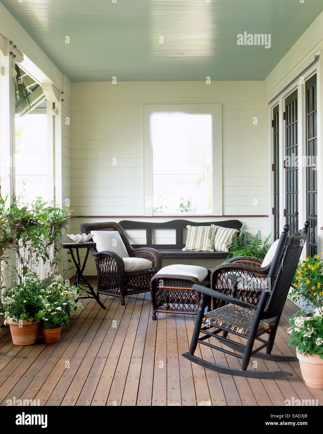 summer porch with flowers and wicker furniture - Stock Image
