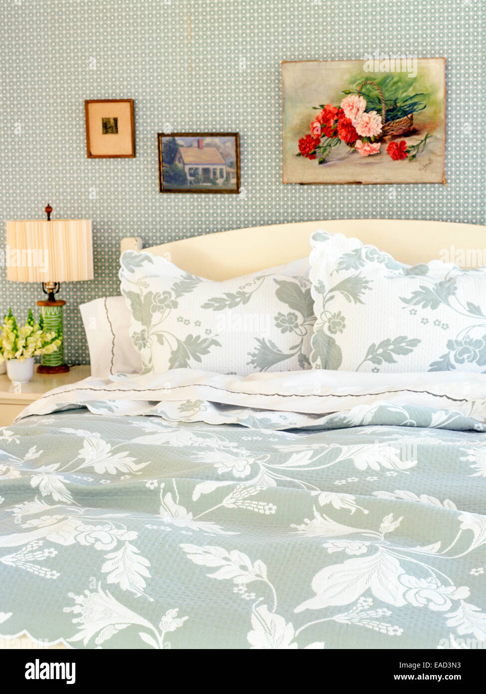 Bed with floral patterned blankets and pillows - Stock Image