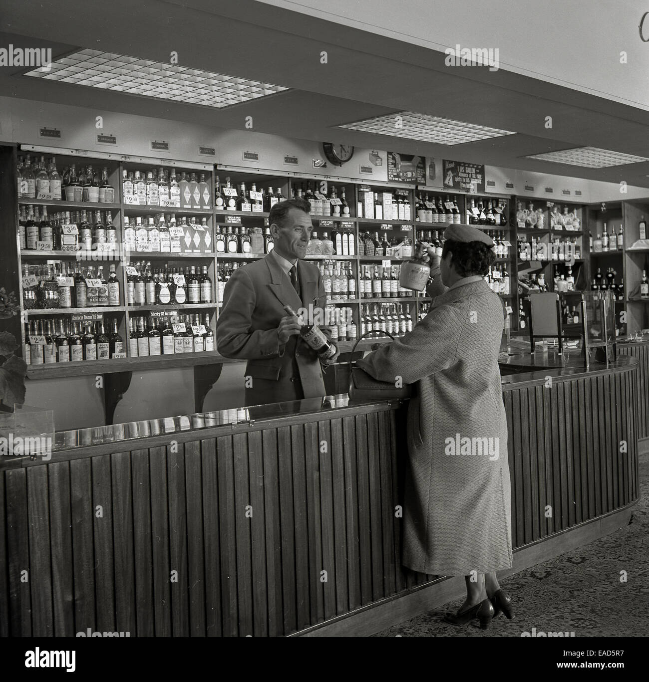 1950s, historical picture of a lady passenger being served at an airport duty free kiosk or shop, Dublin airport, - Stock Image