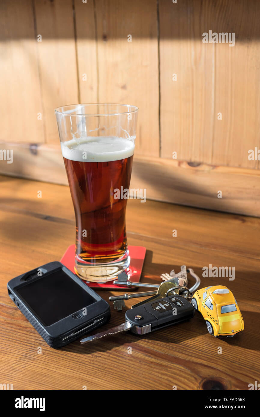 Car keys, pint of beer and a mobile phone. - Stock Image