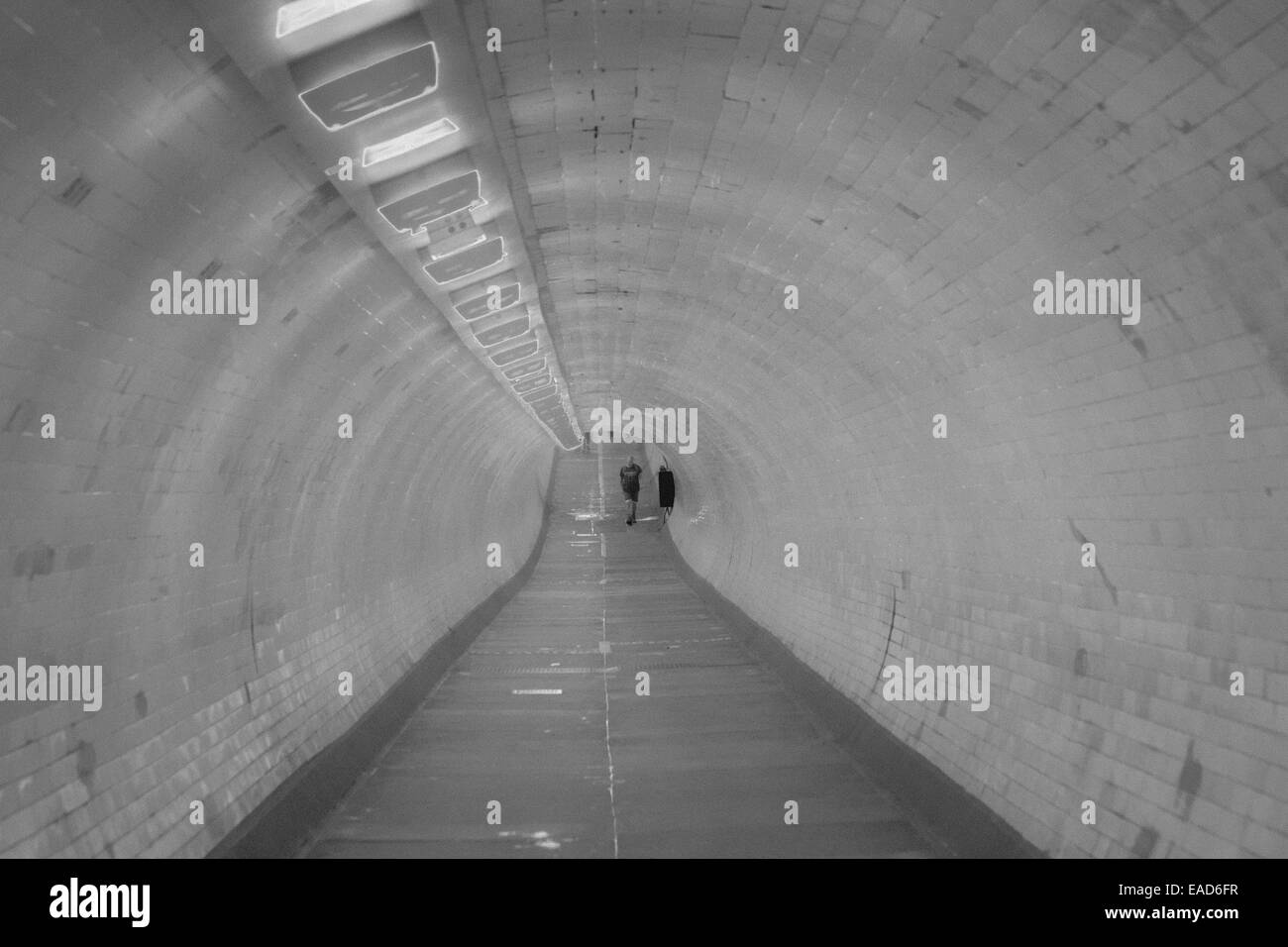 Man walking through Greenwich foot tunnel that runs under the River Thames between Greenwich and Isle of Dogs London - Stock Image
